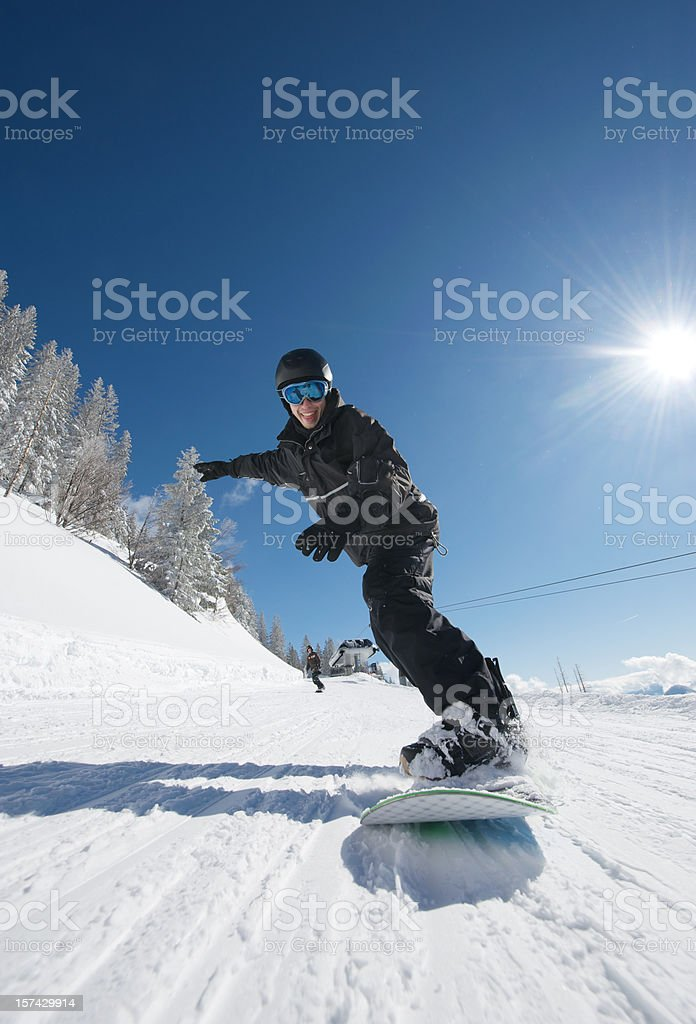 Snowboarder racing on the ski slope - wide angle royalty-free stock photo