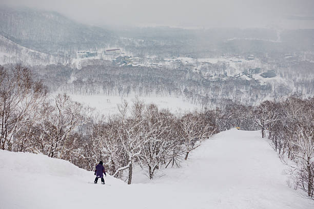 snowboarder riding down the mountain at niseko united, hokkaido, japan - sapporo stock photos and pictures