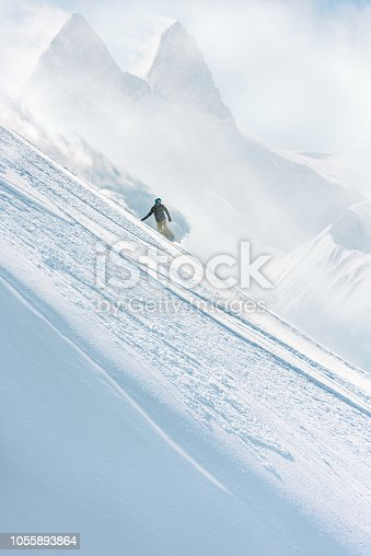 Snowboarder riding on a steep slope in a majestic winter landscape