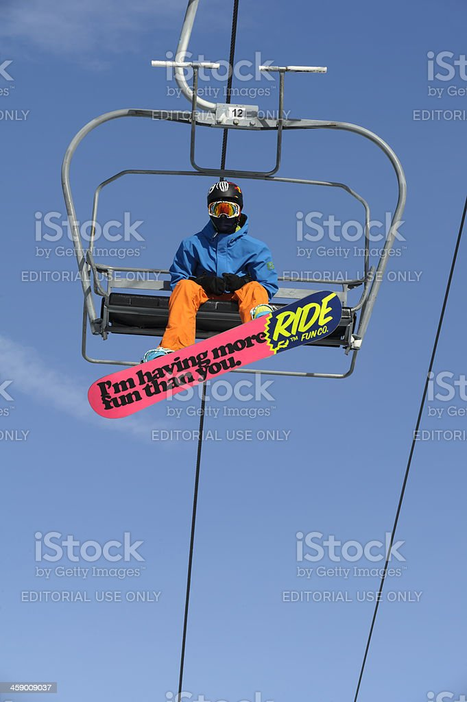 Snowboarder Riding Ski Lift, Fun Saying on Pink Board stock photo