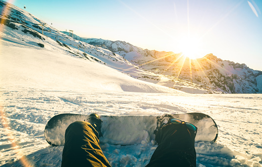 istock Snowboarder sitting at sunset on relax moment in french alps ski resort - Winter sport concept with adventure guy on top of mountain ready to ride down - Legs view point with teal and orange filter 867820086