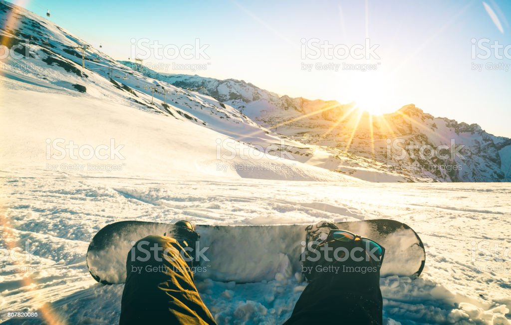 Snowboarder sitting at sunset on relax moment in french alps ski resort - Winter sport concept with adventure guy on top of mountain ready to ride down - Legs view point with teal and orange filter stock photo