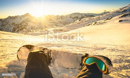 istock Snowboarder sitting on relax moment at sunset in public ski resort - Winter sport concept with person on top of the mountain ready to ride down - Legs view point with warm backlighting filter 858583274