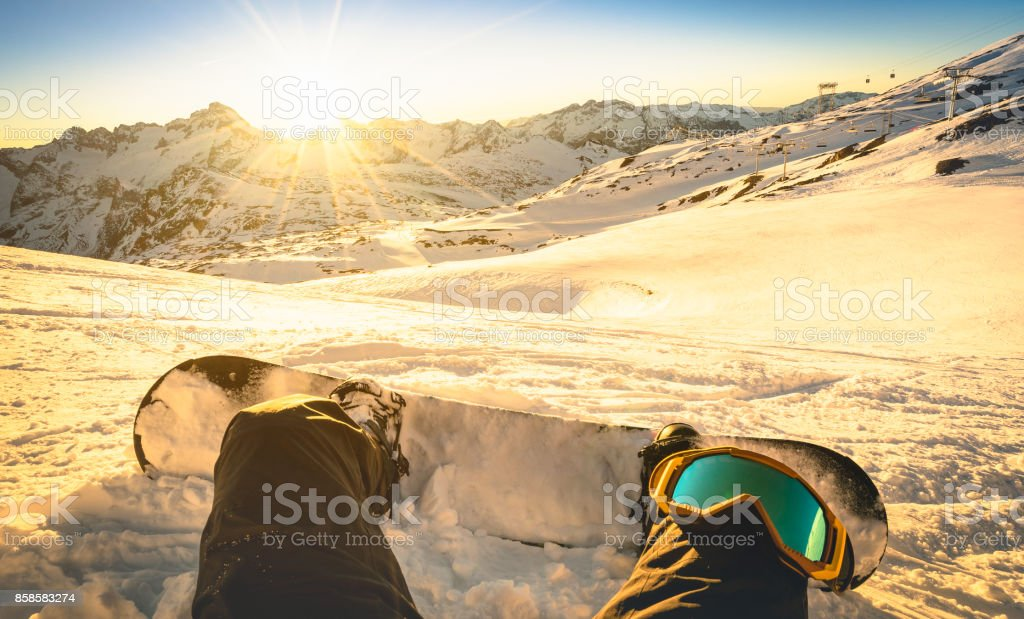 Snowboarder sitting on relax moment at sunset in public ski resort - Winter sport concept with person on top of the mountain ready to ride down - Legs view point with warm backlighting filter stock photo