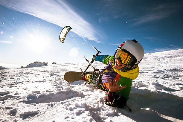 snowboarder skydives on blue sky backdrop in mountains snowfall - kiteboarding - fotografias e filmes do acervo