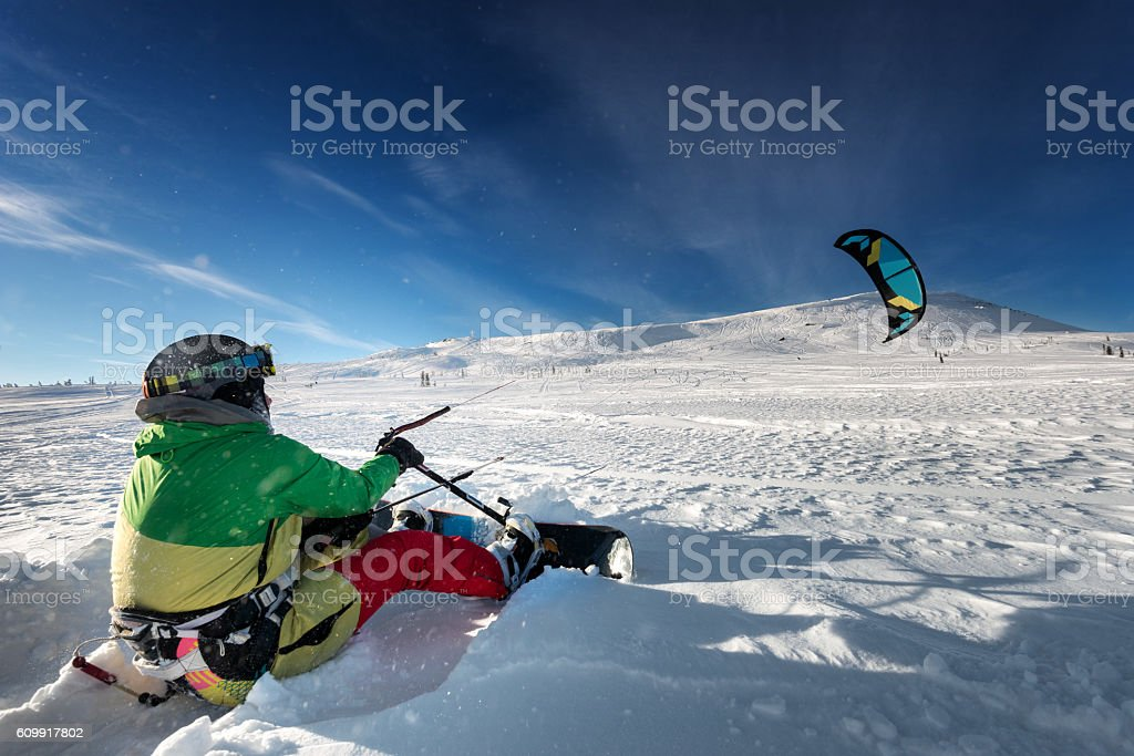 Snowboarder skydives on blue sky backdrop in mountains snowfall stock photo