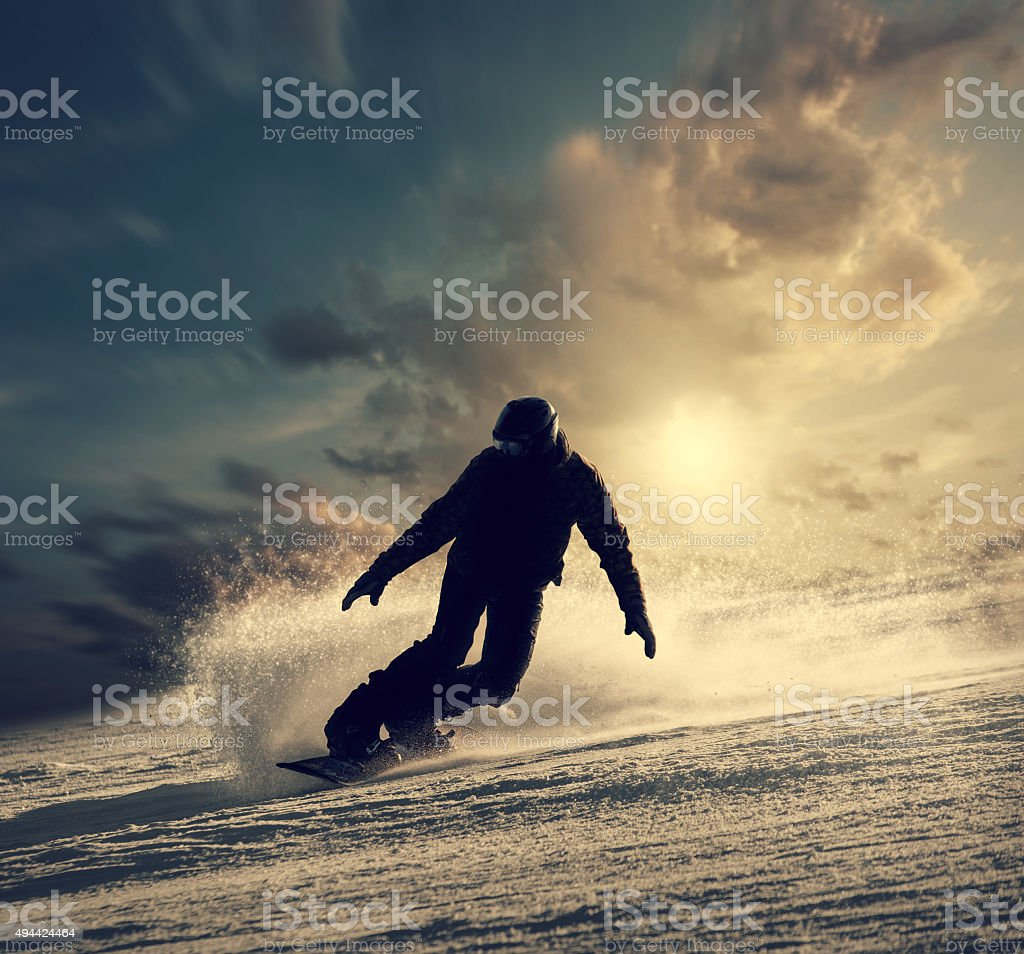 Snowboarder slides down the snowy hill stock photo