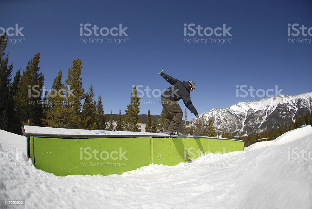 Snowboarder sliding a box in terrain park stock photo