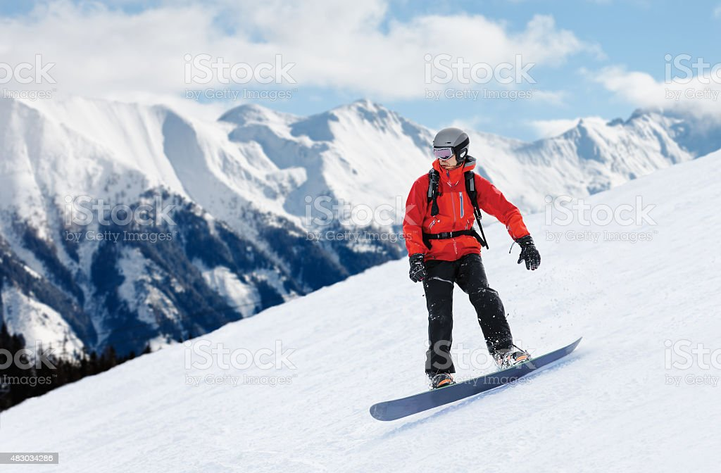Snowboarder sliding down the slope stock photo