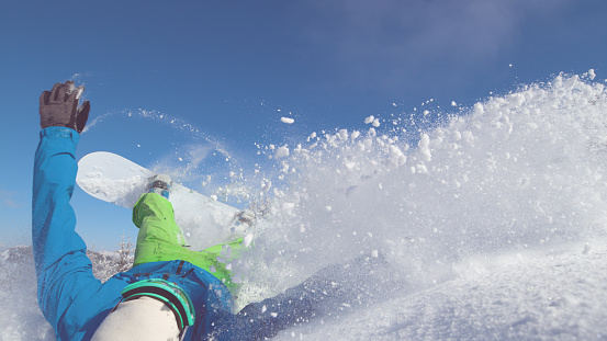 CLOSE UP: Snowboarder speeding down dangerous mountain falls into deep snow.