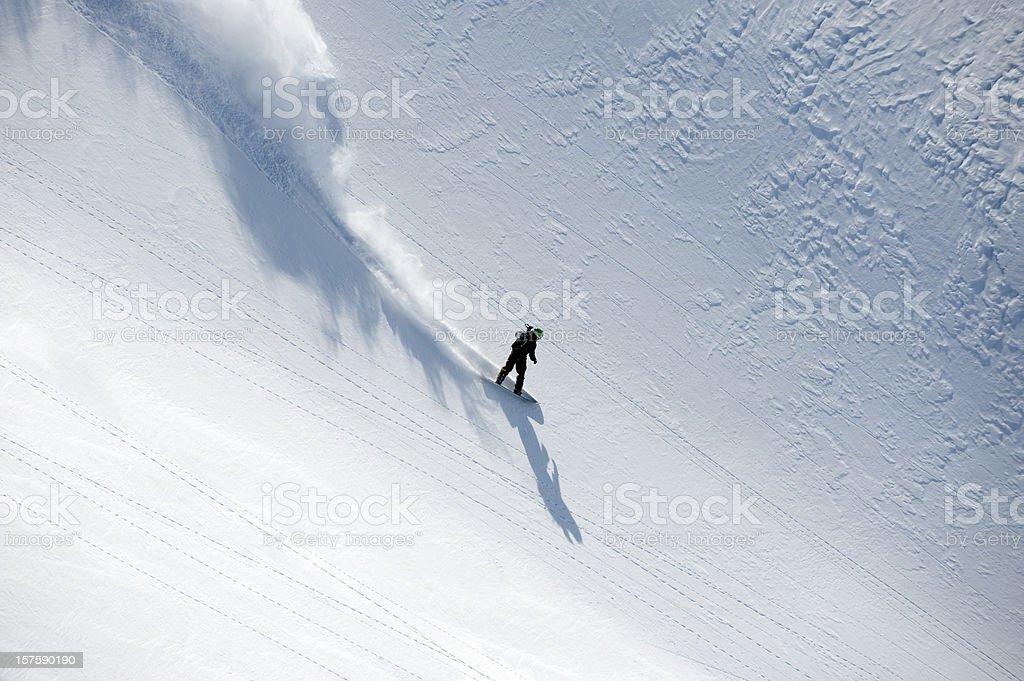 Snowboarder speeding down hill in powder snow flowing behind stock photo