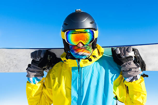 snowboarder standing on snow mountain slope snowboarder close up on snow mountain slope hold snowboard wear sport suit helmet and ski wear goggles over blue sky copy space ski goggles stock pictures, royalty-free photos & images