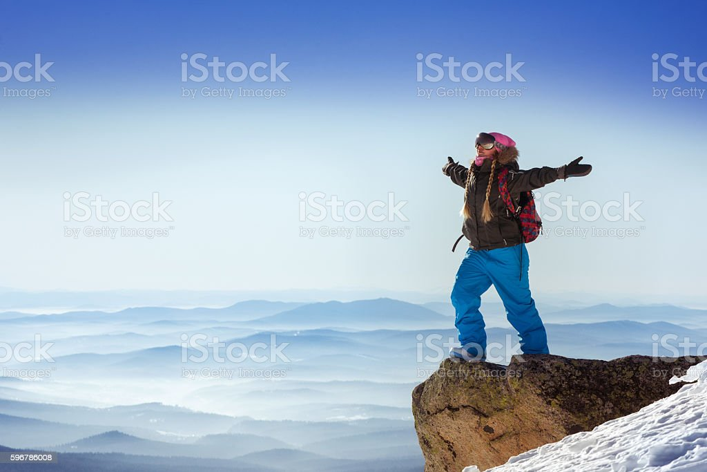 Snowboarder stands in winner pose on the top of mountain stock photo
