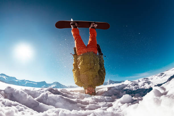 Snowboarder stands on head against mountains