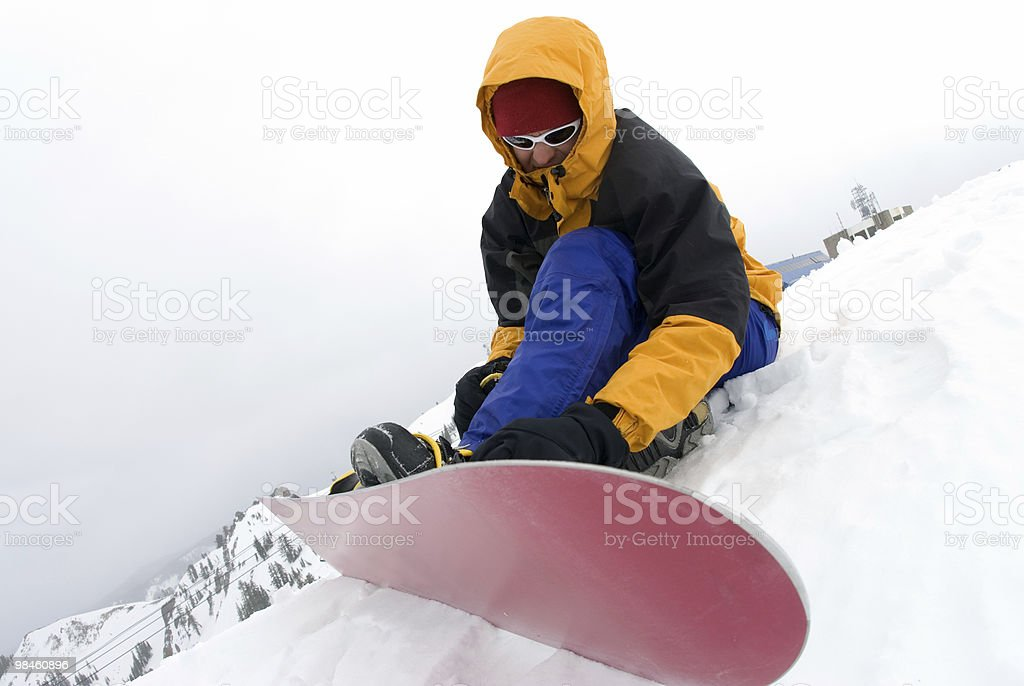 Snowboarder strapping on board royalty-free stock photo