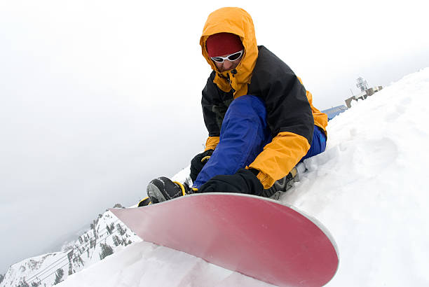 Snowboarder strapping on board stock photo