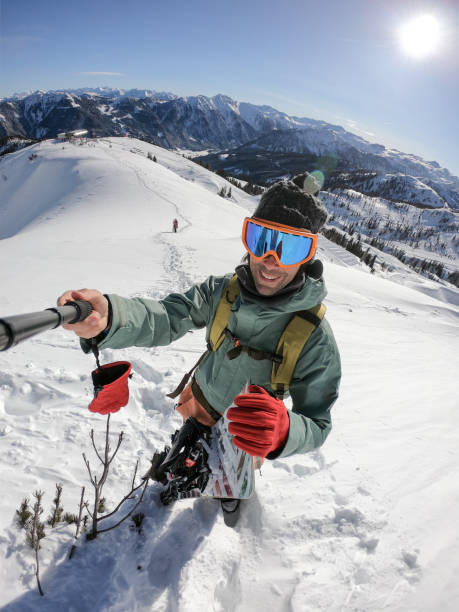 Snowboarder taking selfie on top of the mountain stock photo