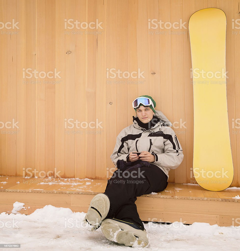 Snowboarder texting while waiting for his friends stock photo