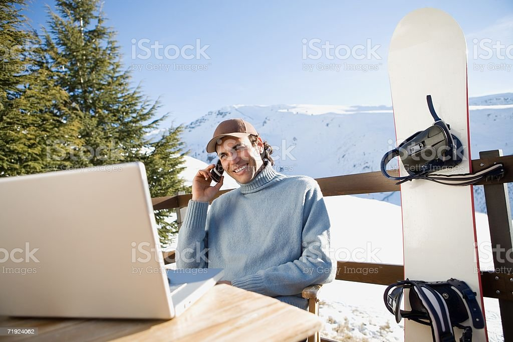 Snowboarder using laptop royalty-free stock photo