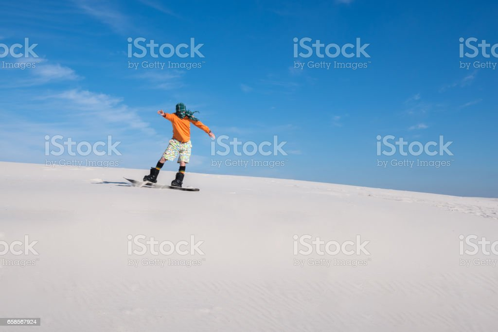 Snowboarder Wearing A Scarf Rides On Sand Dune Stock Photo