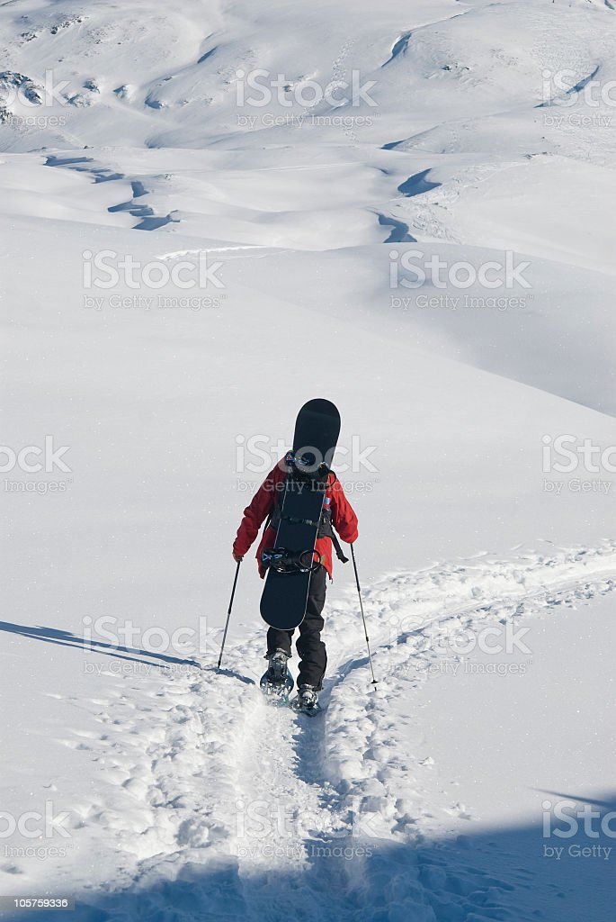 Snowboarder with his board on the back royalty-free stock photo