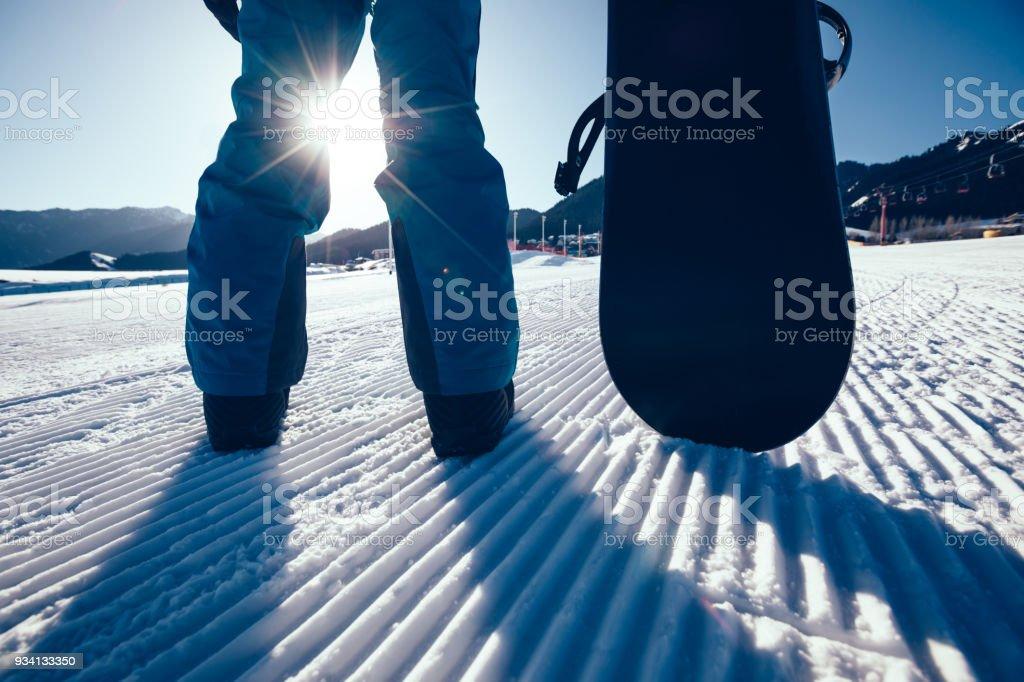 snowboarder with snowboard stand on ski piste in winter mountains – zdjęcie