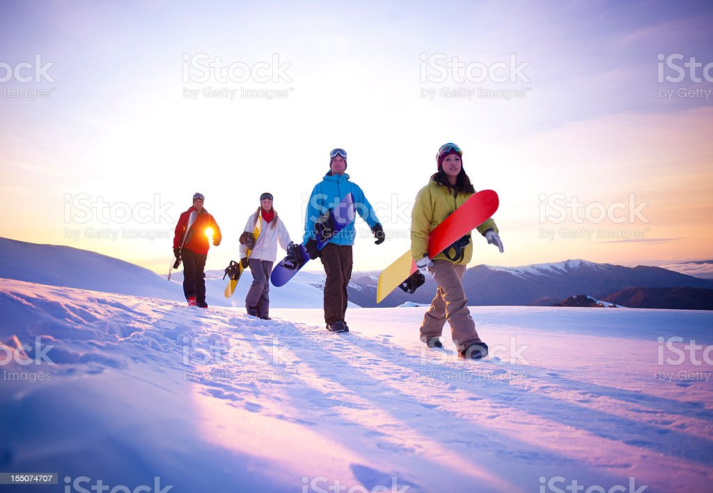 Snowboarders climbing a snowy mountain in the early morning royalty-free stock photo