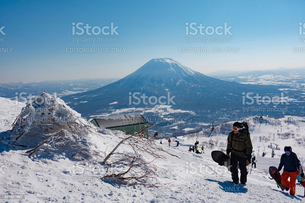 Snowboarders Hike up the Backcountry Trail at Niseko United stock photo