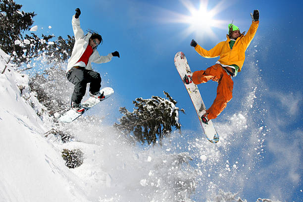 snowboarders jumping against blue sky - young singles stock photos and pictures