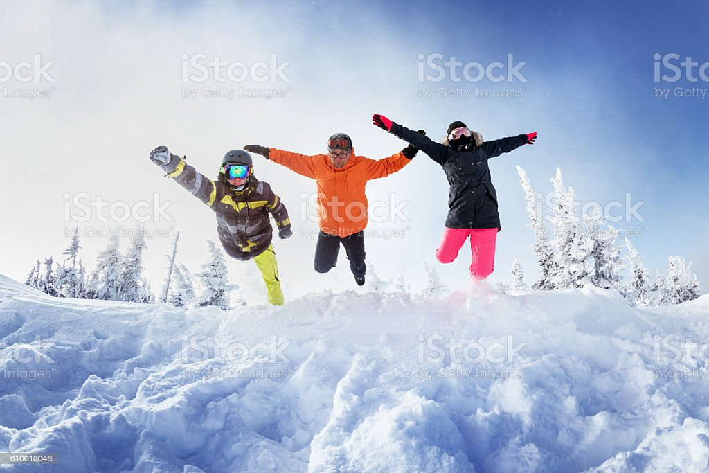 Snowboarders posing on blue sky backdrop in mountains stock photo