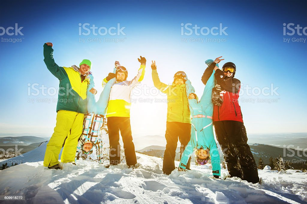 Snowboarders posing on blue sky backdrop in mountains skiing stock photo