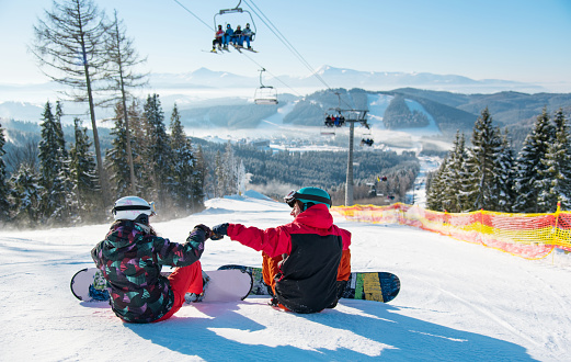 Snowboarders resting on the top of the ski slope under the ski lift at winter resort with a beautiful scenery of the Carpathian mountains and forests on a sunny day