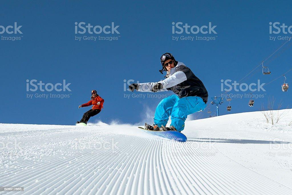 Snowboarders ride on blue sky backdrop in mountains - foto de stock