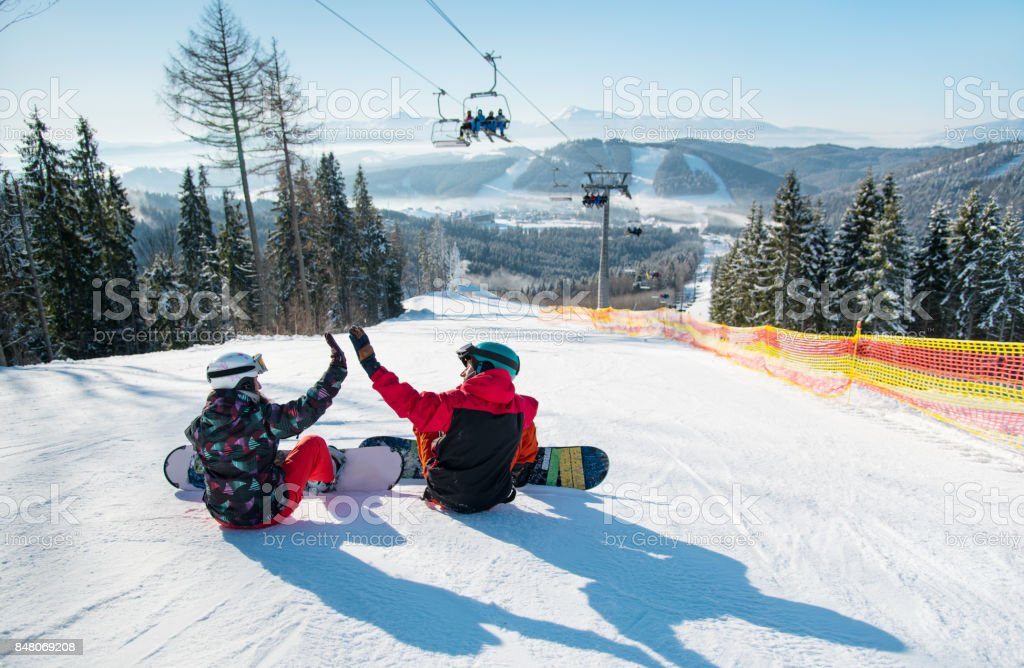 Snowboarders sit on the top of the ski slope under the ski lift let's high five to each other with a beautiful scenery of mountains and forests on a sunny morning stock photo