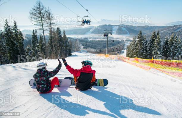 Photo of Snowboarders sit on the top of the ski slope under the ski lift let's high five to each other with a beautiful scenery of mountains and forests on a sunny morning