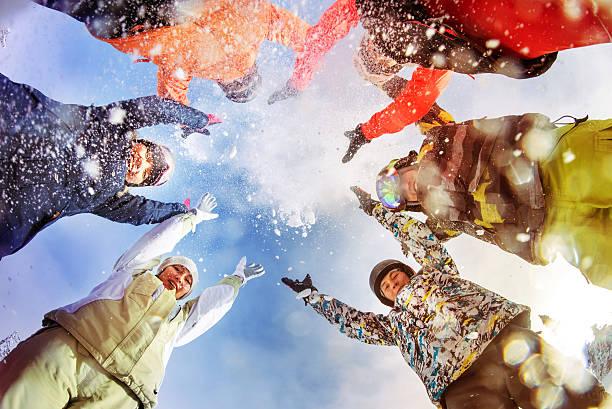 Snowboarders throw snow on blue sky backdrop stock photo