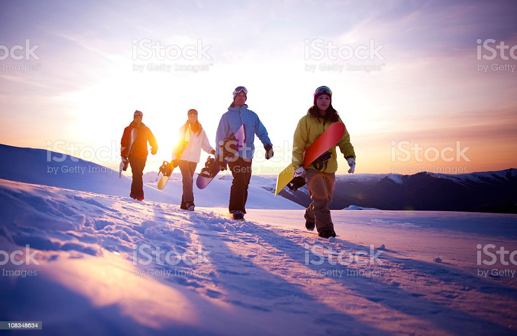 Snowboarders walking in snow with sun rising in background royalty-free stock photo