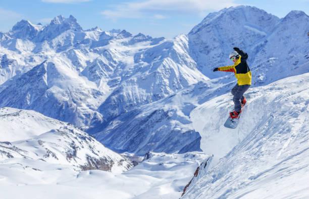 Snowboarding down the mountain's top stock photo