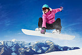 Girl in pink and black clothes snowboarding.