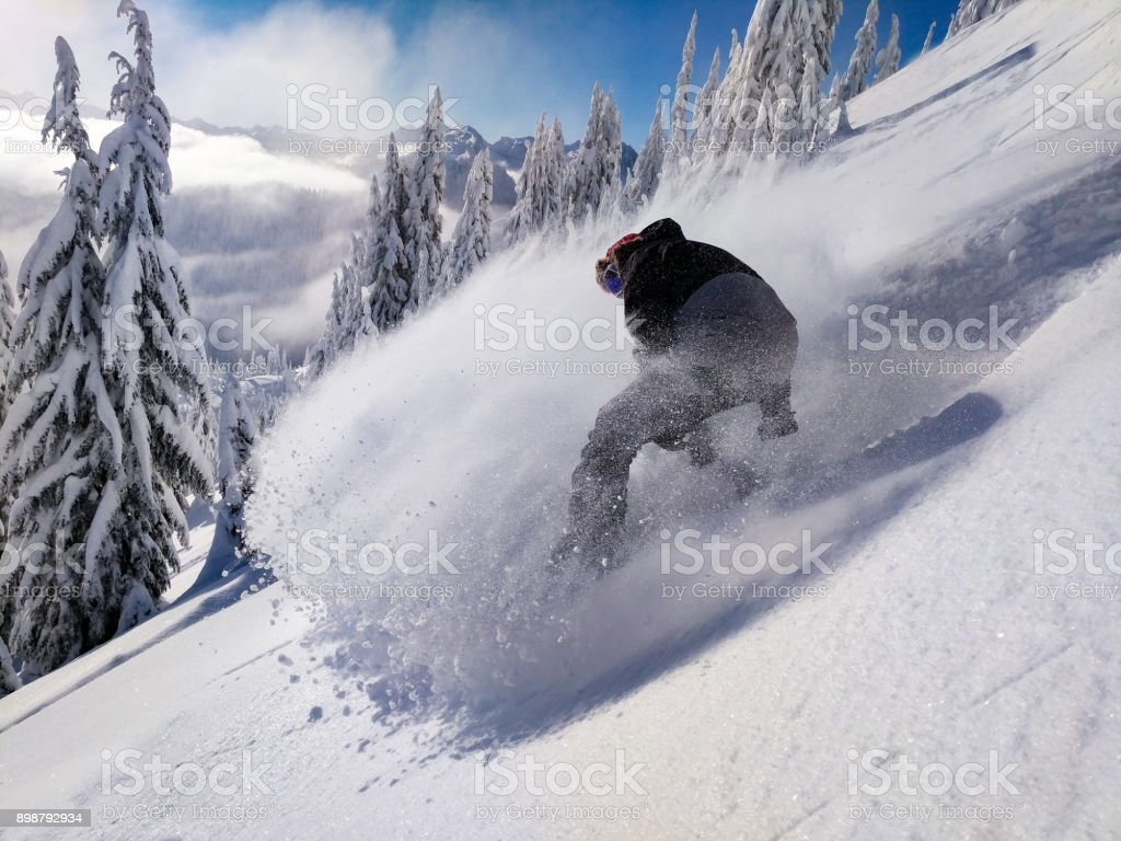 Snowboarding Powder Snow Spray Sunny Winter Day at Stevens Pass Washington stock photo