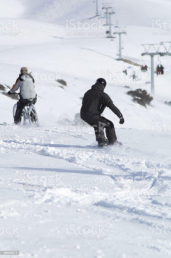 Snowborder and biker downhill royalty-free stock photo