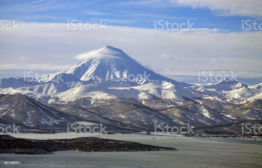 Snowborder and ships aganst Vilyuchinsky volcano . stock photo