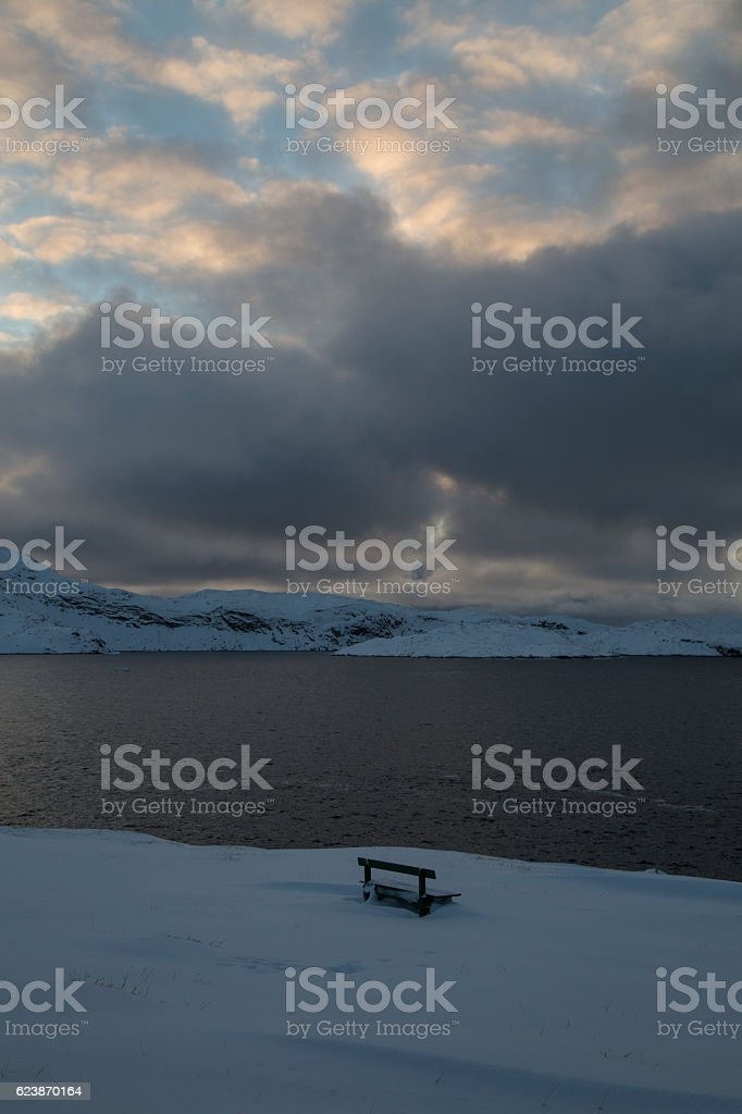 Snowbound park bench overlooking the ocean and a cloudy sky stock photo