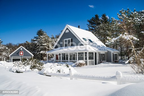A small home and garage are covered with a fresh coating of snow during a Cape Cod Winter.