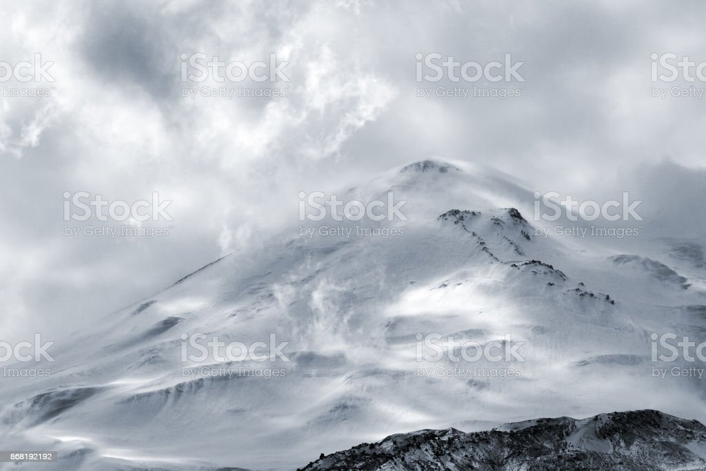 Snow-capped Elbrus mountain surrounded by clouds rises above the mountain area in Kabardino-Balkaria (Caucasus, Russia). stock photo
