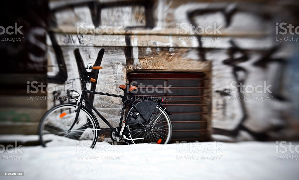 Snowcapped Green Bicycle Leaning Against Wall in Berlin during Winter royalty-free stock photo