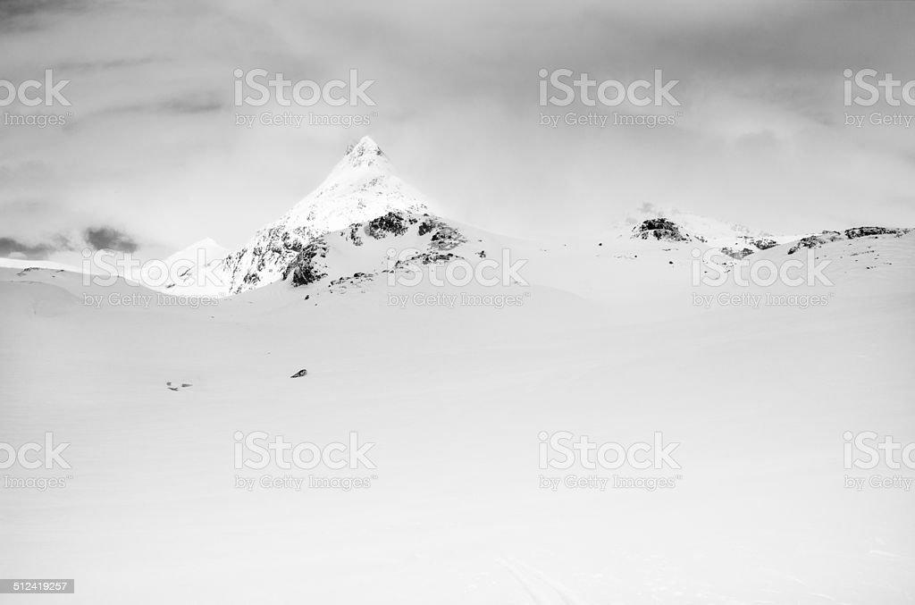 Snowcapped mountain peak lit by sun in Jotunheimen National Park stock photo