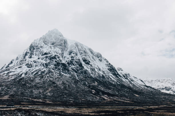 Snowcapped mountains in Scottish Highlands near Glen Coe, Scotland. Snowcapped mountains in Scottish Highlands near Glen Coe, Scotland, on a foggy spring day. north coast 500 stock pictures, royalty-free photos & images