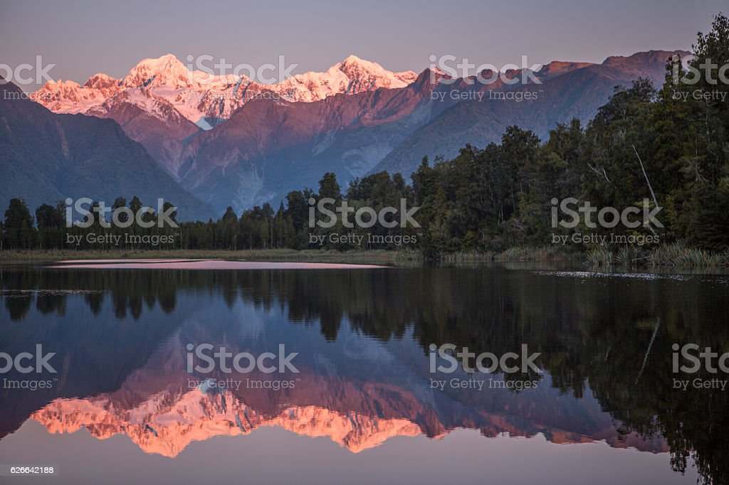 Snowcapped Mountains Reflected In Tranquil Lake stock photo