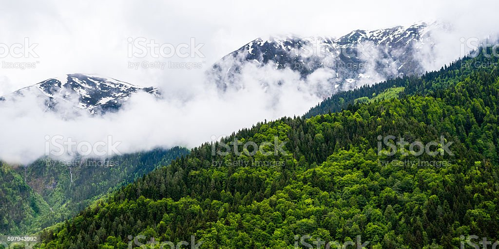 Snowcapped mountains veiled with clouds stock photo